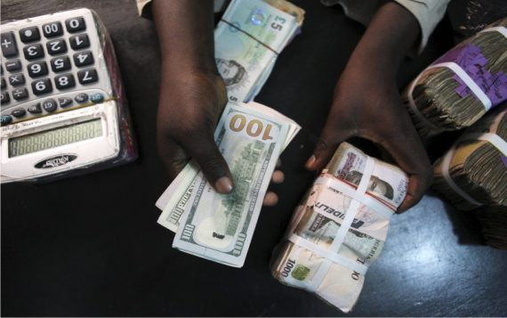 Bureau de change worker holding Dollar and Naira notes
