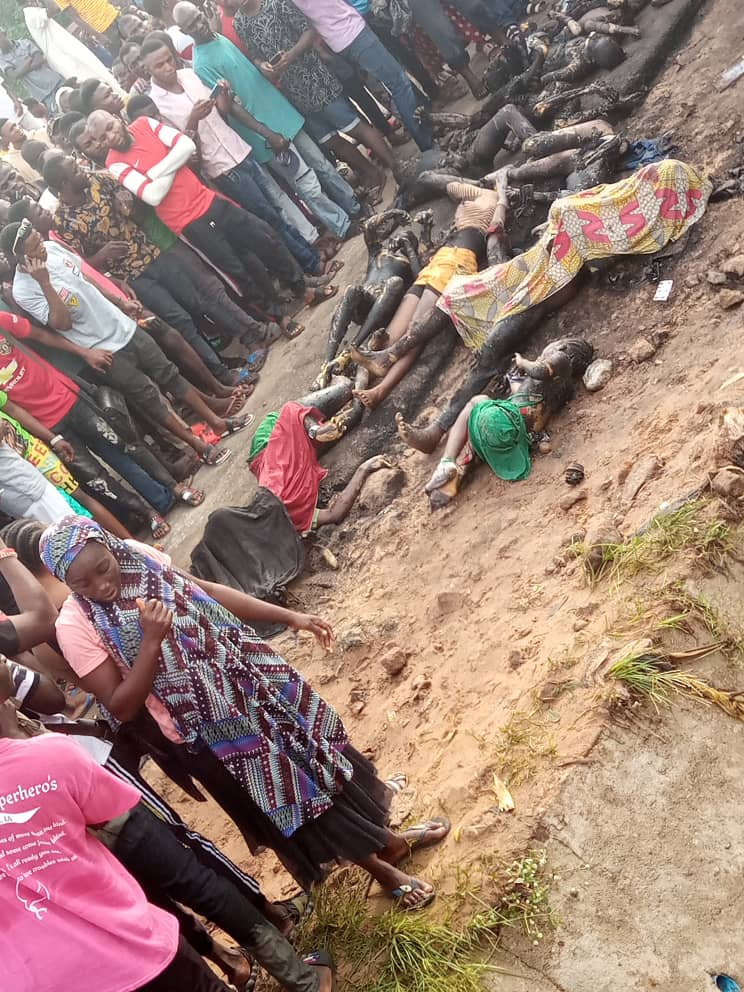 Onlookers at the scene of the Lokoja explosion, with victims bodies on the ground