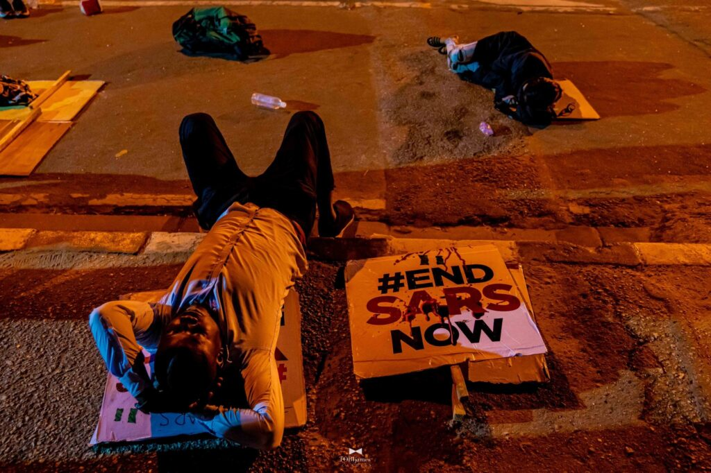 Protester sleeps on the ground with an #ENDSARSNOW placard beside him