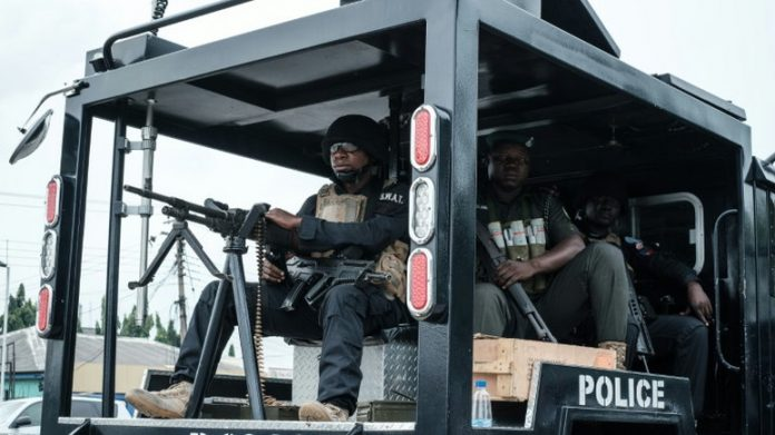 Nigeria Police officers inside a police van, wearing combat gear