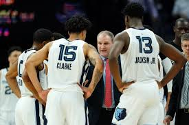 basketball team talking game-play with their coach